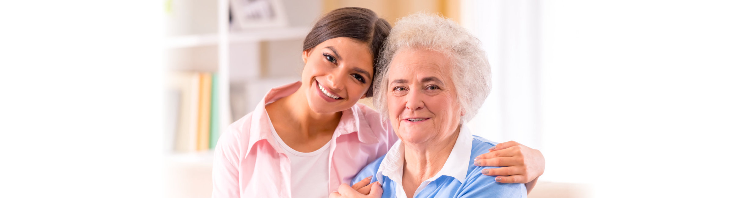 Caregiver of senior woman at home sitting on the couch