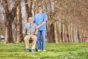 A man in a wheelchair and a caregiver